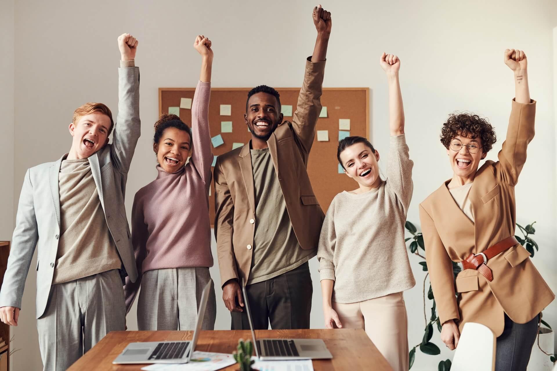 cinq jeunes gens qui fêtent leur succès et leur joie d'avoir booster la confiance en eux au travail